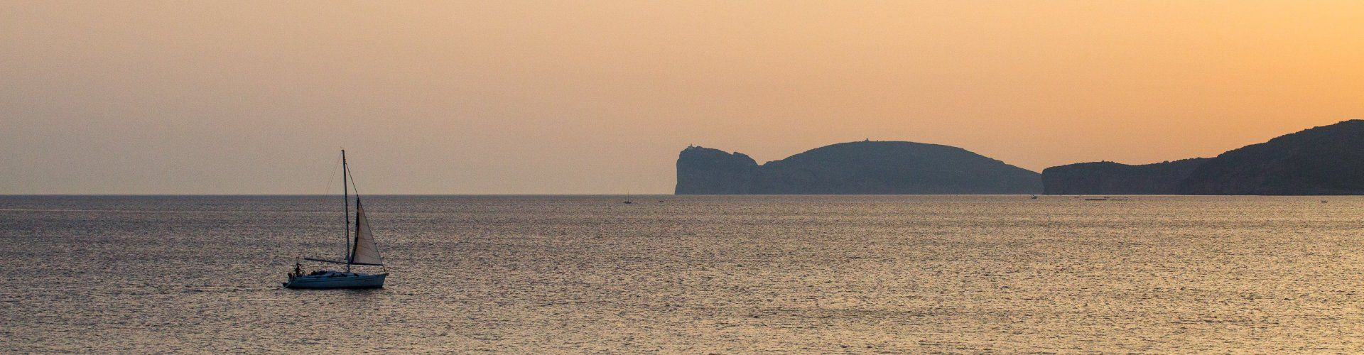 The sea seen from Alghero at sunset with a sailing boat and Capo Caccia on the horizon