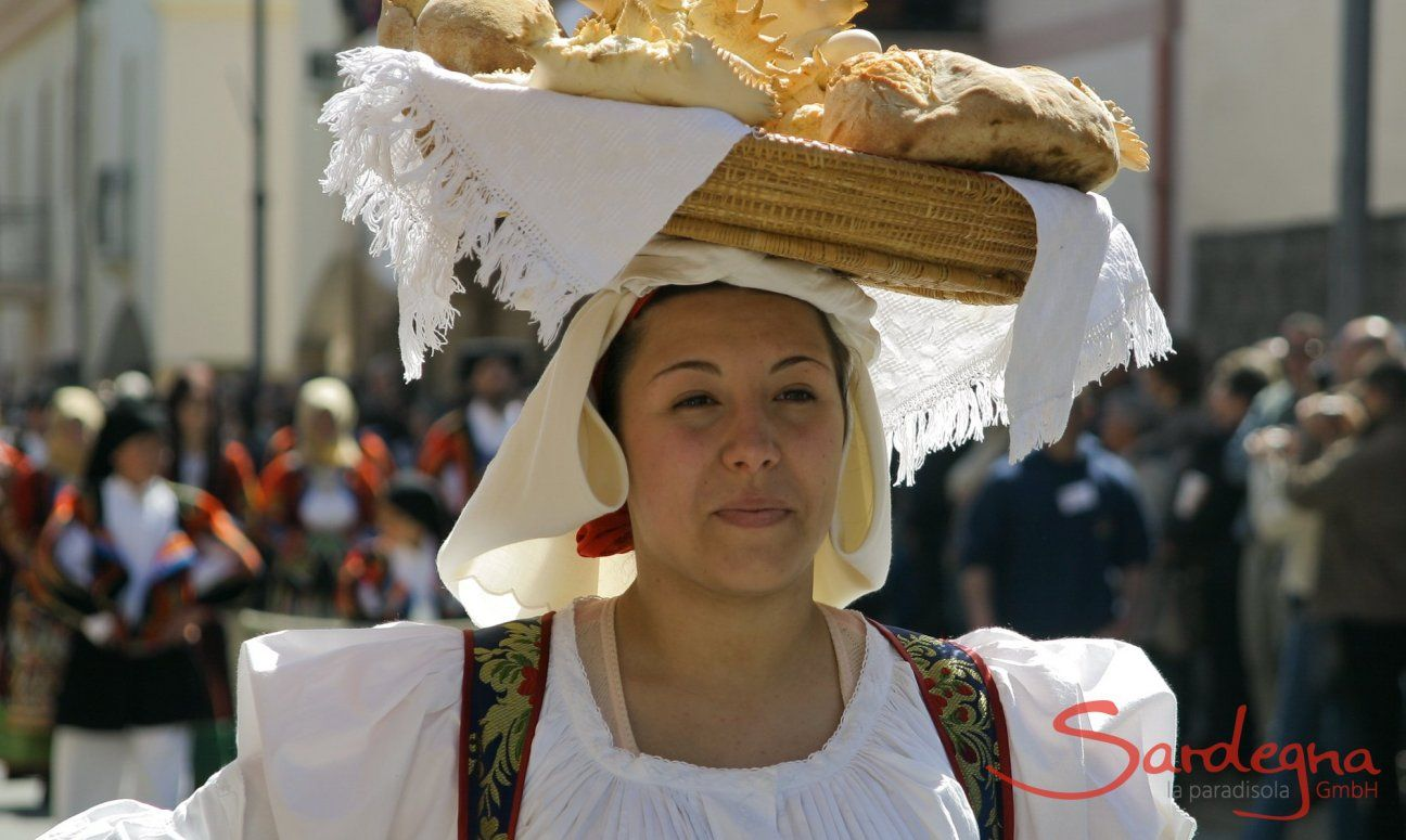Woman in sardinian costume who is carrying a basket full of bread on her head