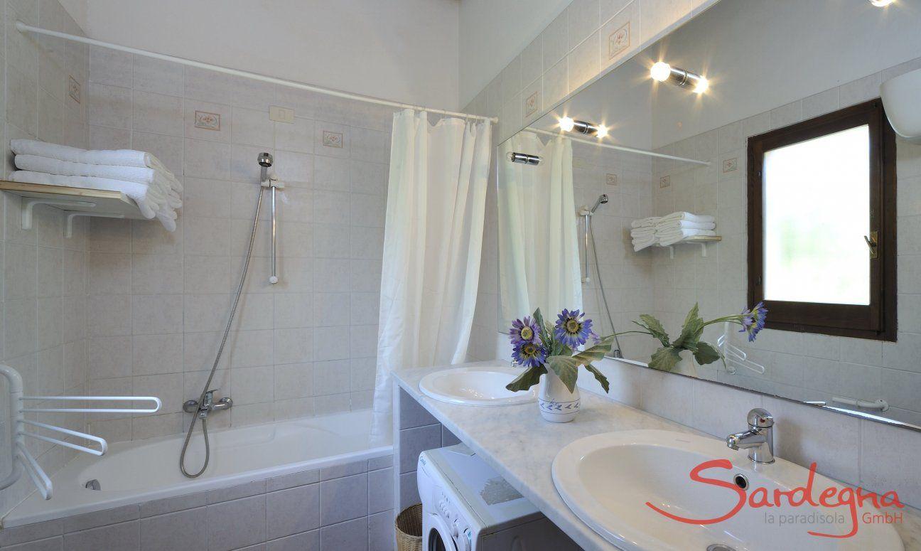 Bathroom with bathtub, two sinks and washing machine