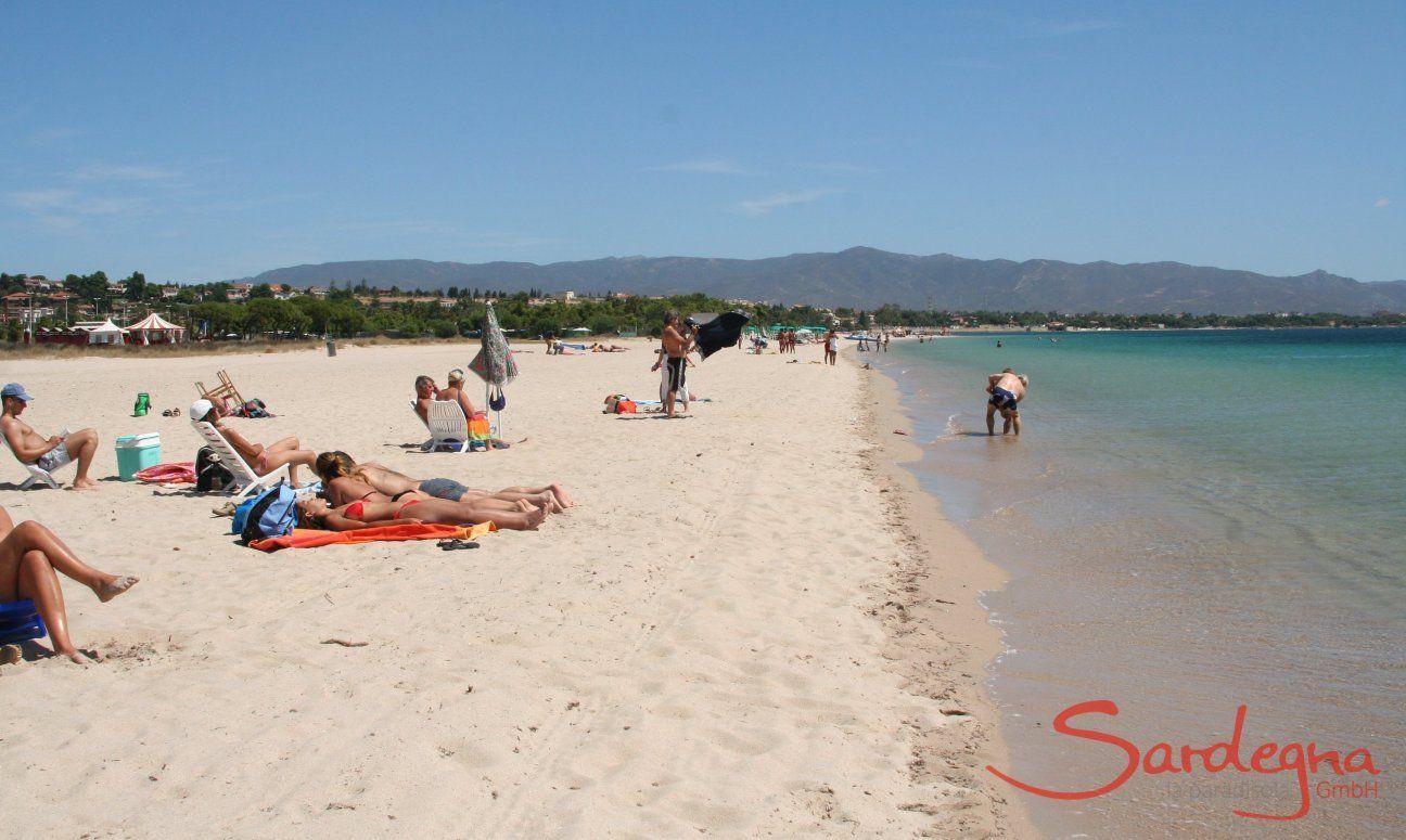 Taking a sunbath on the white sand of the beach Poetto close to Cagliari