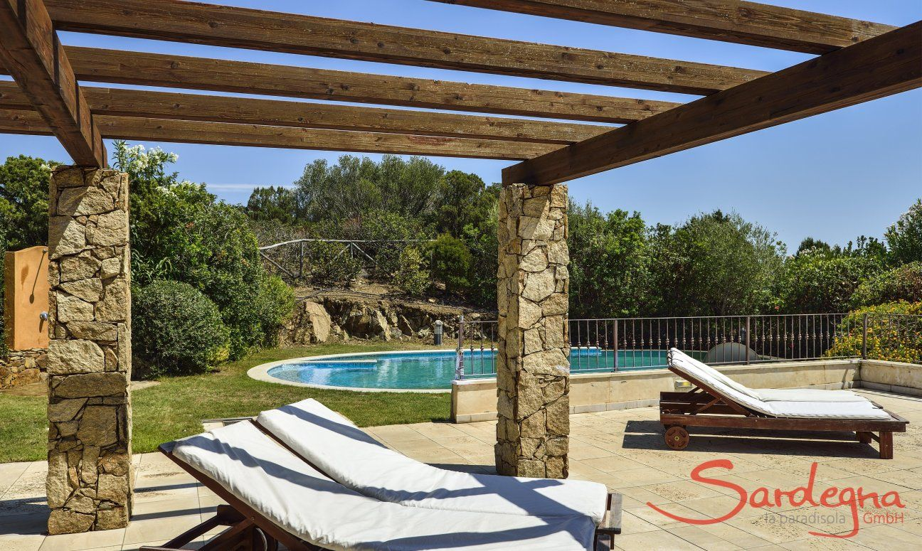 Sunbeds on the terrace and the pool in the background