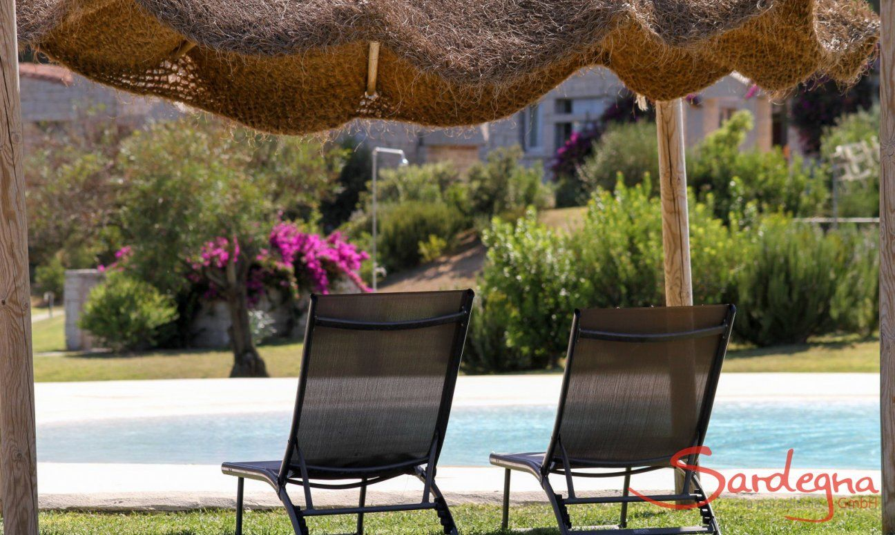 Sunbeds underneath an ombrella by the pool of Li Conchi