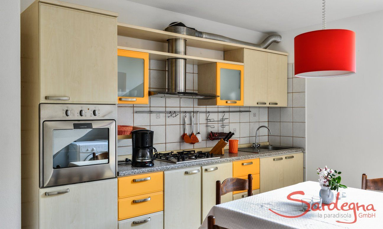 Kitchen souterrain with all essential devices like oven, gas stove sink, exhaust hood