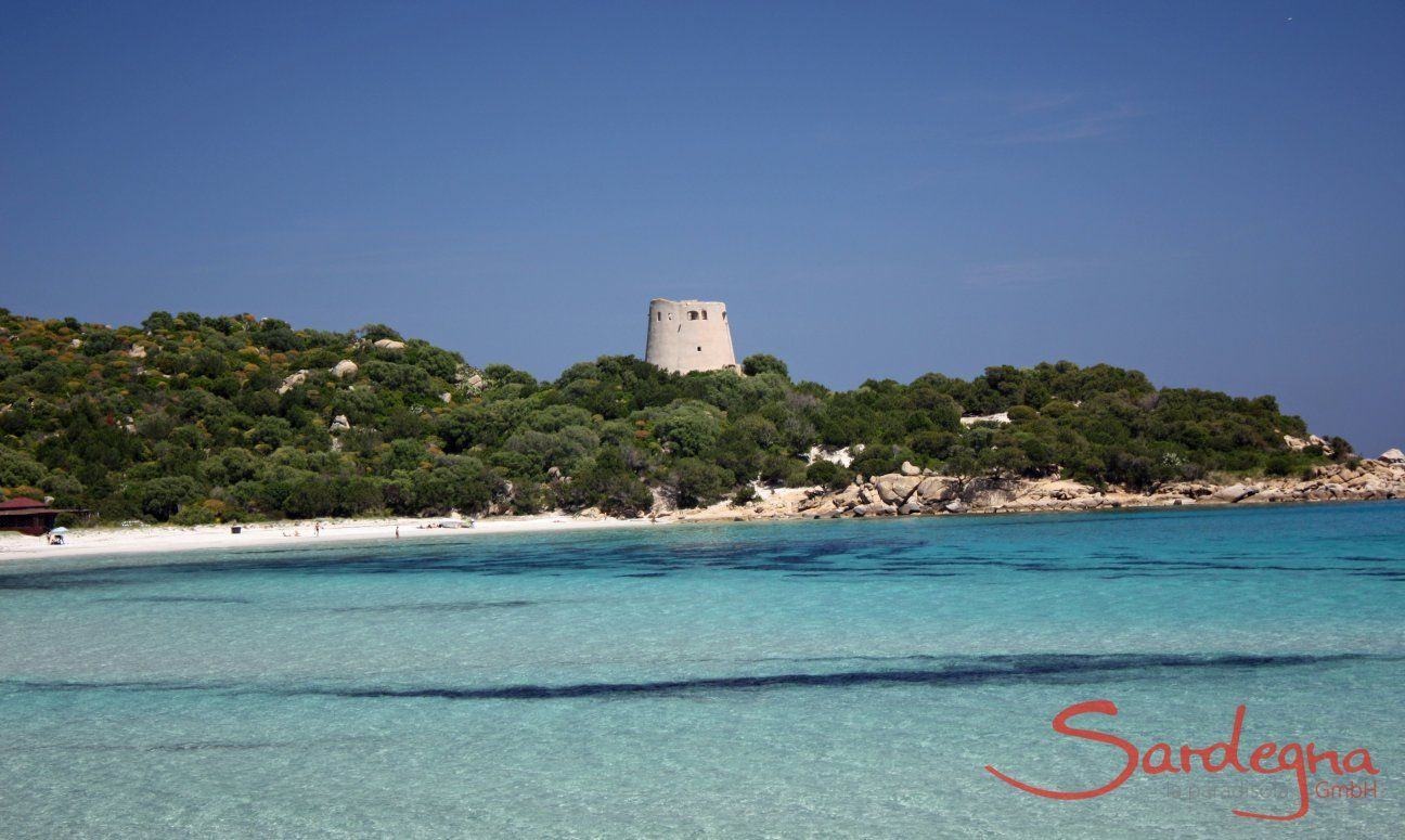 Crystal clear water, white sand and the old spanish tower in the bay of Cala Pira