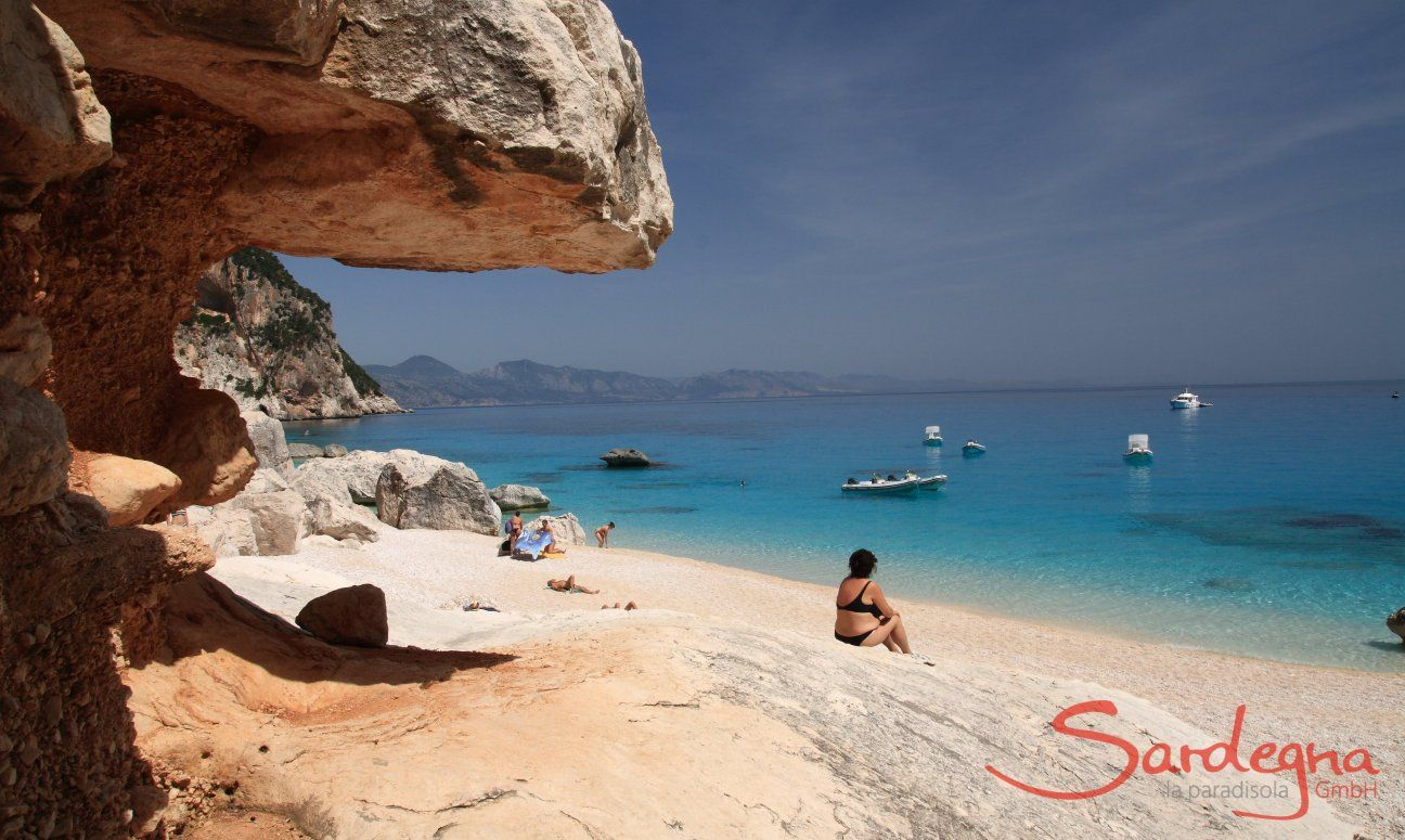 Visitor is sitting on the beach in front of the rocks of Cala Luna and looks over the sea