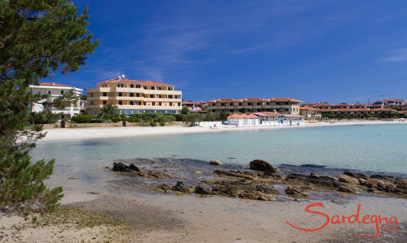 White beach and transparent sea just in front of the skyline of Golfo Aranci