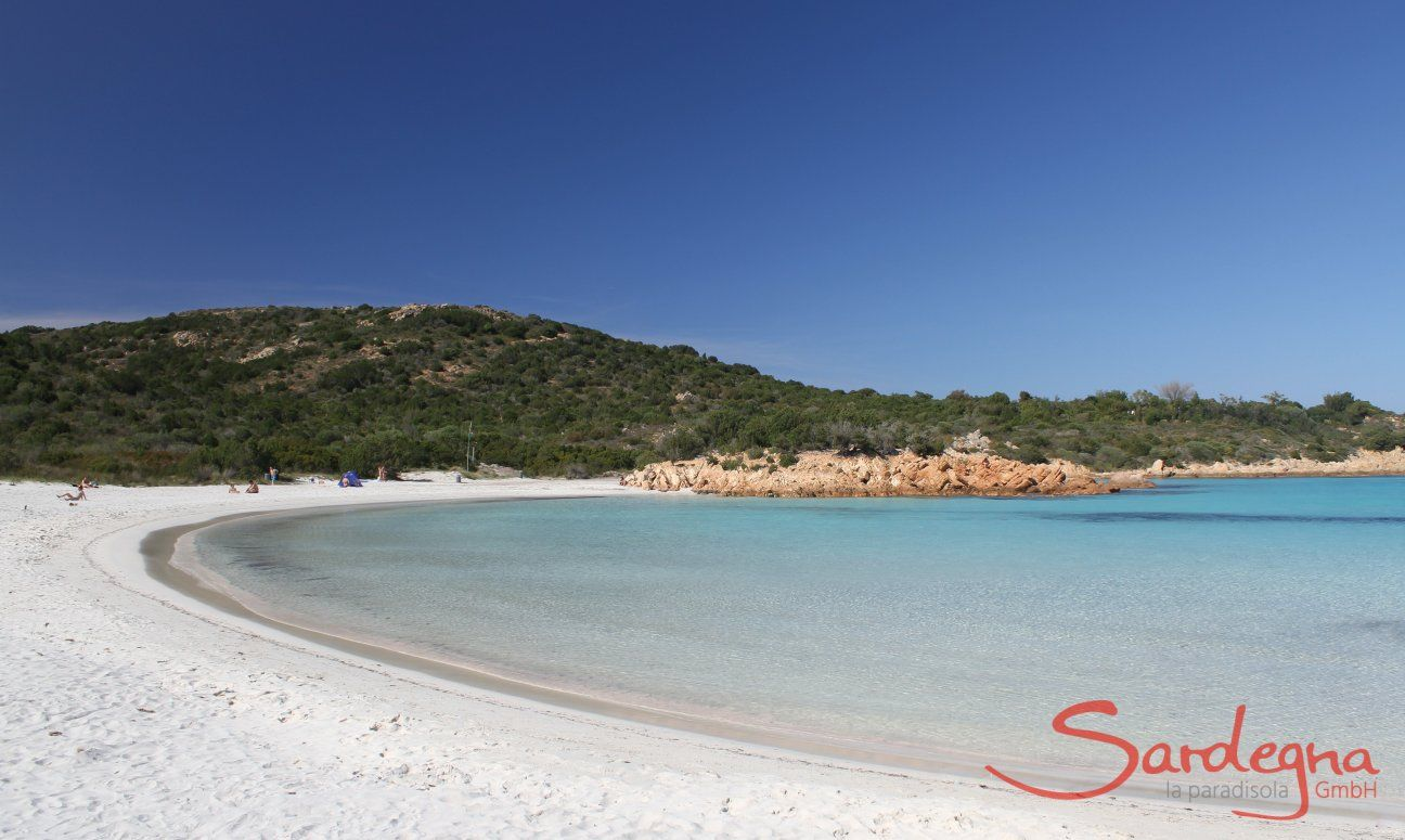Halfmoon bay of Romazzino with white sand ending in yello coloured rocks and a hill covered in green macchia