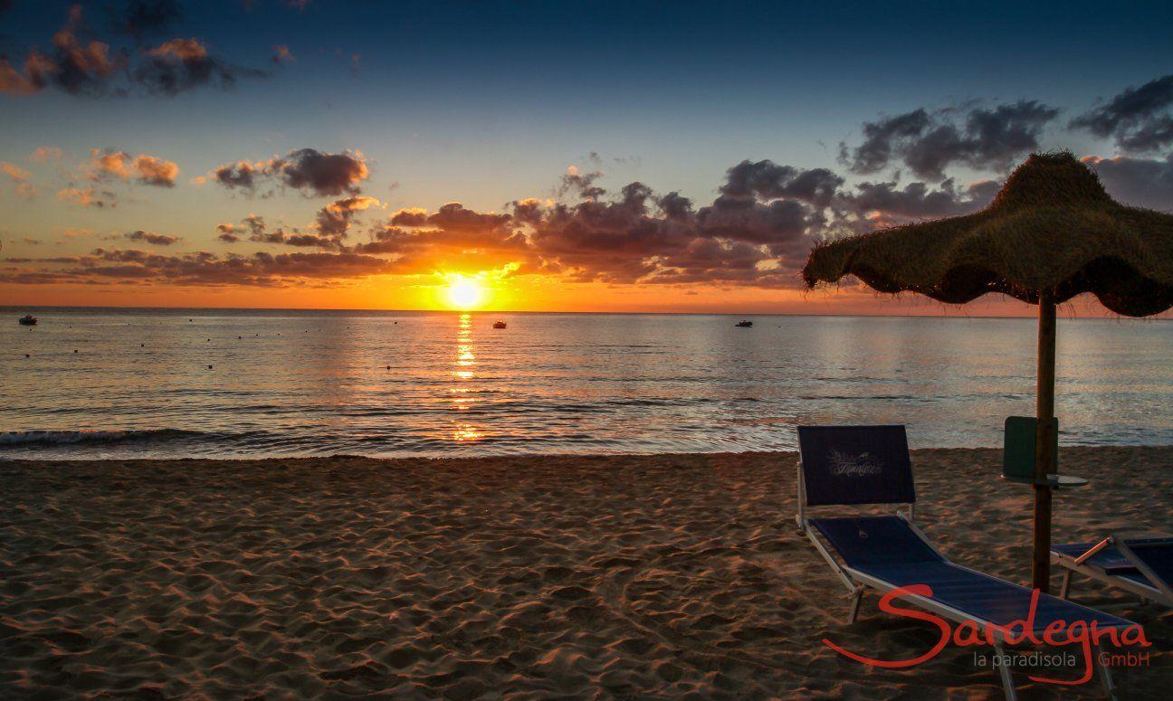 The sunrise over the sea of Cala Sinzias stings the horizon in bright orange