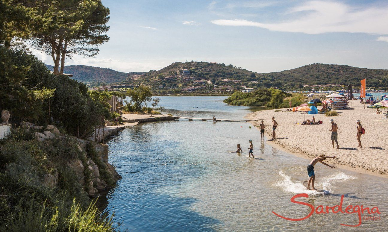 Kids play in the shallow water of the lagoon of Porto Taverna