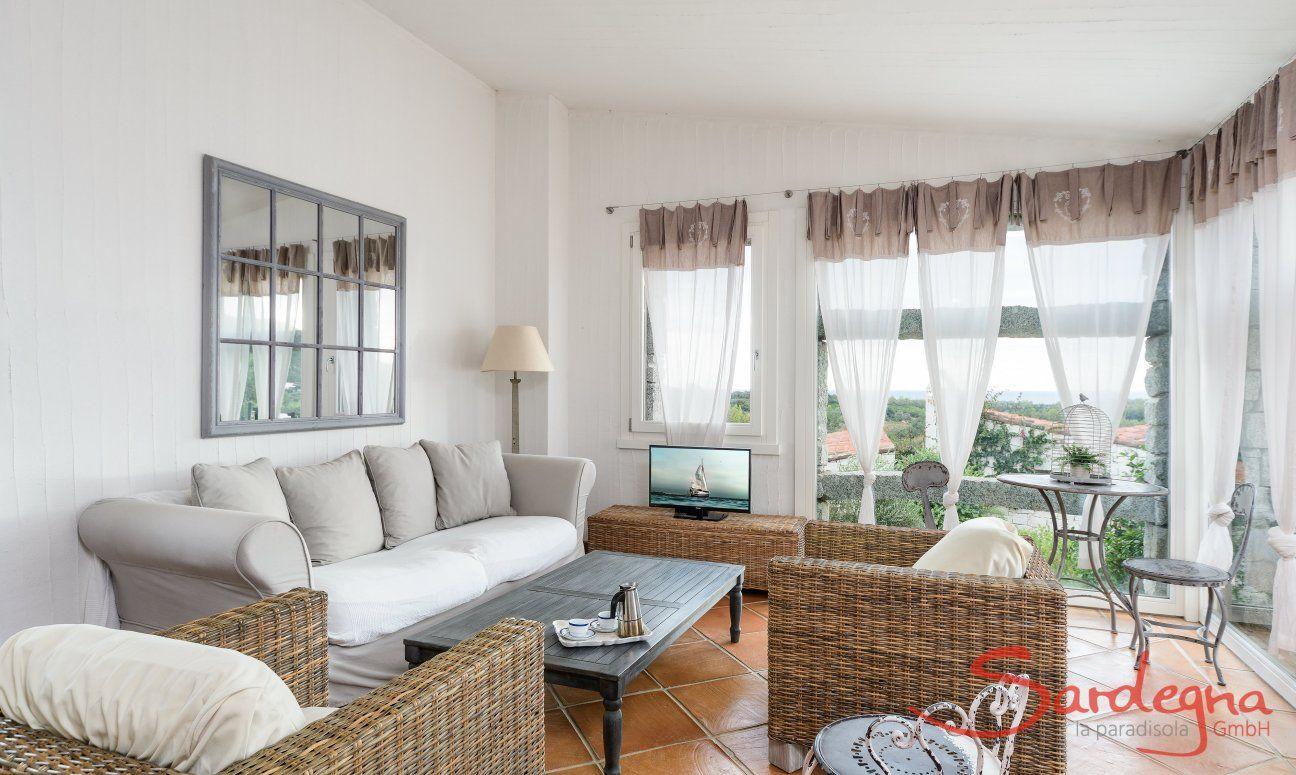 Living area with sofa, armchairs, TV and big panoramic window