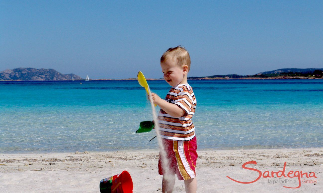 Child playing with the white sand of Porto Istana, 7 miles south of Olbia