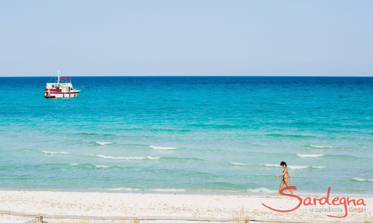 A woman walks on the white sand beach of La Cinta with the light blue sea with a boat in the background