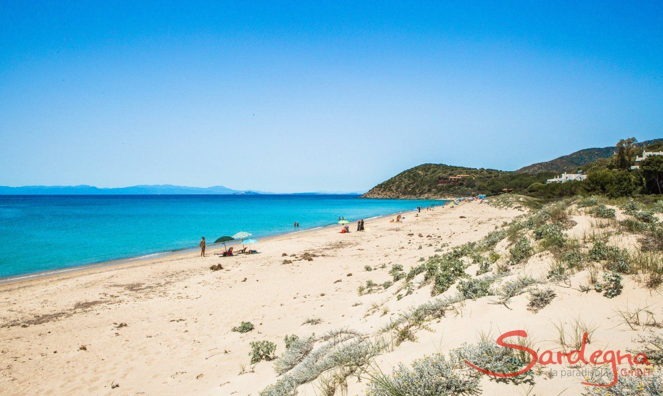 Large white, sandy beach of Geremeas with blue sea and coastline of Cagliari