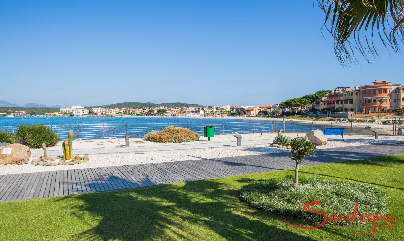 Citybeach with grass and white sand at the harbour of Golfo Aranci