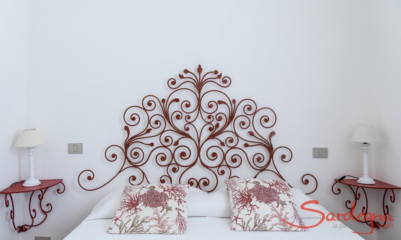 Bed with red, wrought iron  	bed-headand night tables in  Su Faru 2 Pula