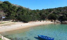 Traditional, blu fisherboat floats on the crystal clear water of the bay of Cala Moresca, Golfo Aranci