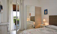 Bedroom with double bed, cupboard and door to the terrace  Villa Campidano 21
