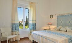 Bedroom with double bed and fabrics decorated in sardinian style Li Conchi 9, Cala Sinzias