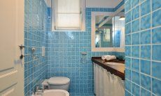 Bath with light blue tiles and shower Li Conchi 9, Cala Sinzias
