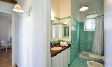 Bath with shower and light green tiles, Li Conchi 9, Cala Sinzias