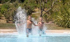 Two boys jump into the pool of Li Conchi, Cala Sinzias
