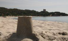 Close up of the sandmodel of the spanish tower of Cala Pira, in the background the real tower