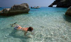Young girl snorkelling in the transparent water of Cala Goloritze