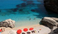 Three red ombrellas offering shade on the white sand beach of Cala Goloritze
