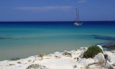 Beach in the south of Sardinia with turquoise water and sailing ship