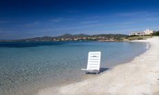 White sun lounger in the crystal clear water on the beach of Golfo Aranci