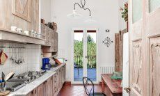 Fully equipped kitchen with a little table and terrace access