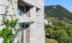 Window in the granite wall and green surroundings
