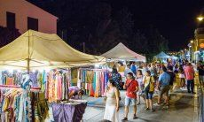 Stand selling colourful cloths on the streetmarket taking place on warm summernights in Golfo Aranci