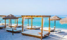 Luxurious sunbeds and parasols on the beach Maria Pia close to Alghero