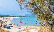 Just a few ombrellas and people even in high season on the beach of Feraxi, Capo Ferrato