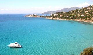 Bay of Torre delle Stelle, on the crystal clear sea hovers a small yacht
