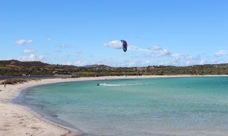 Beach of Lu Impostu with kite surfer